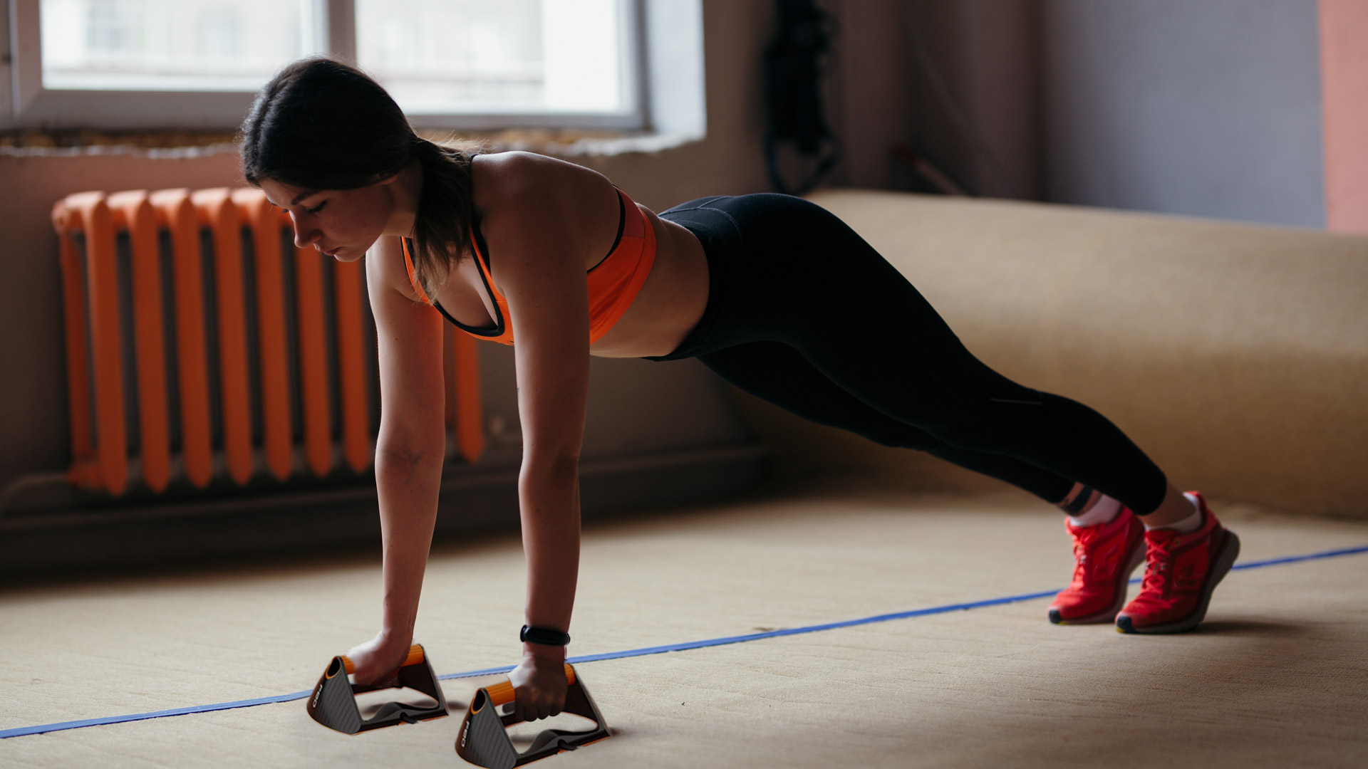 woman using push-up bars at home for fully upper-body workout